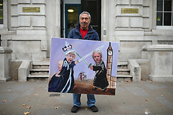 © Licensed to London News Pictures. 03/09/2019. London, UK. Artist Kaya Mar poses outside the Cabinet Office with a new piece of satirical artwork showing the Queen, Speaker John Bercow and Prime Minister Boris Johnson. MPs return from recess today and may vote on legislation to block a no deal exit from the European Union. Photo credit: Rob Pinney/LNP