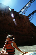 Meghan Walcott soaks in the sun on the first day of the raft trip down the colorado.  The bridge is called Navajo Bridge
