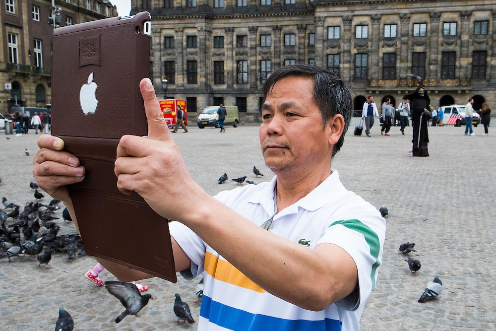 Nederland, Amsterdam, 13 mei 2014<br /> Toerist maakt een foto met een ipad.<br /> Foto (c) Michiel Wijnbergh