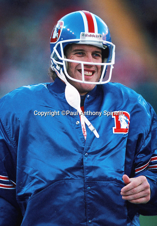 Denver Broncos quarterback John Elway (7) smiles on the sideline during the NFL football game against the Los Angeles Raiders on Dec. 2, 1990 in Denver. The Raiders won the game 23-20. (©Paul Anthony Spinelli)