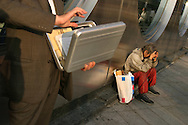 "A ""homeless' man sits outside a bank, in the Shinjuku district of Tokyo, whilst beside him a business man opens his briefcase, Japan."