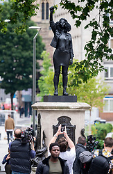 "© Licensed to London News Pictures; 15/07/2020; Bristol, UK. People view and photograph a new statue of a black lives matter protestor, Jen Reid, which has been placed on the plinth from where the statue of slave trader Edward Colston was pulled down with ropes and thrown into Bristol docks on 07 June during an All Black Lives/Black Lives Matter protest that made headlines around the world. The new sculpture is titled ""A Surge of Power (Jen Reid) 2020"" by artist Marc Quinn and is made of black resin and steel and was put up around dawn this morning without any permission from Bristol City council. Jen Reid was at the previous protest on 07 June which was in protest for the memory of George Floyd, a black man who was killed on May 25, 2020 in Minneapolis in the US by a white police officer kneeling on his neck for nearly 9 minutes. The killing of George Floyd has seen widespread protests in the US, the UK and other countries. Photo credit: Simon Chapman/LNP."