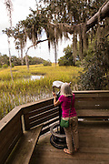 Elderly woman uses a binocular viewer on salt marsh boardwalk at Honey Horn Plantation on Hilton Head Island, SC