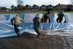 © London News Pictures. Staines, UK. 15/02/2014.<br /> Soldiers from  2nd Royal Tank Regiment and The Gurkhas   installing Geodesign flood barriers in Staines, which have been brought in from Sweden to help control flood waters. The barriers were designed by Sten-Magnus Kullberg (pictured in set).  Photo credit: Ben Cawthra/LNP