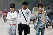 Chinese teenagers in modern casual western clothes walking in a street in Yangshuo, China