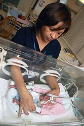 Neonatal Transport Nurse checking positioning of premature baby boy in incubator in Nottingham City Hospital,