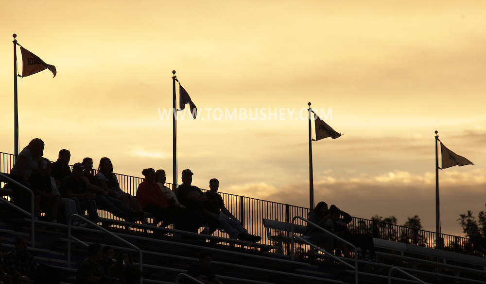 Fans sit in the bleachers at Middletown's Faller Field before the start of a football game between Pine Bush and Middletown on Friday, Sept. 14, 2012.