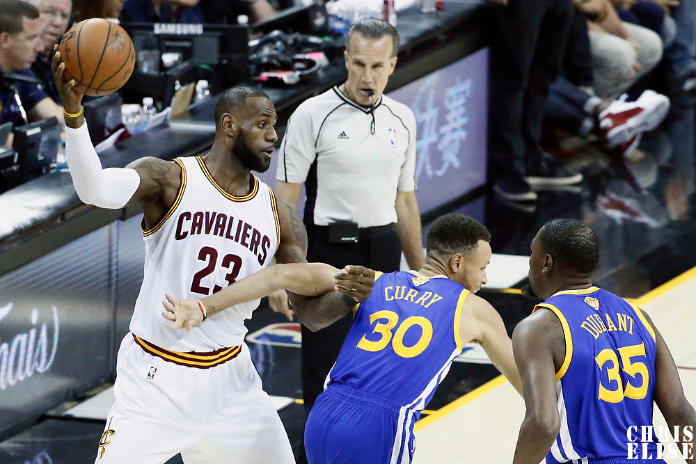 07 June 2017: Cleveland Cavaliers forward LeBron James (23) looks to passes the ball over Golden State Warriors guard Stephen Curry (30) and Golden State Warriors forward Kevin Durant (35) during the Golden State Warriors 118-113 victory over the Cleveland Cavaliers, in game 3 of the 2017 NBA Finals, at  the Quicken Loans Arena, Cleveland, Ohio, USA.