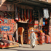 A Moroccan man in traditional Berber dress walks past a carpet shop in the souks of Marrakech, Morocco.