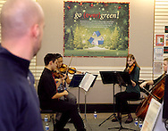 A visitor watches Centerville High School Orchestra members (from left) Justin Lun, Run Wei Wang, Caroline Danzi and Margaret Otto perform holiday music at the WashingtonCenterville Public Library in Centerville, Monday, December 5, 2011.