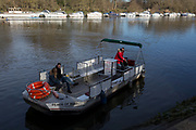 Two passengers on Hammerton's Ferry, cross the river Thames between Marble Hill House on the north bank, and Ham on the southern bank, on 3rd February 2019, in London, England. Hammertons Ferry was originally opened in 1908 by Walter Hammerton and its current owners are Mr & Mrs Francis Spencer in July, 2003. The whole family are currently involved in all aspects of the business, however the daily running of the Ferry is by father & son, Francis & Andrew Spencer. Hammerton's is a pedestrian and cycle ferry service across the River Thames in the London Borough of Richmond upon Thames, London, England. The ferry links the northern bank near Marble Hill House in Twickenham with the southern bank near Ham House in Ham. Foot passengers pay £1 with children and bikes paying 50p and it is one of only four remaining ferry routes in London not to be replaced by a bridge or tunnel.