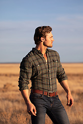 good looking man outdoors at sunset in a field