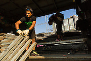 19 JANUARY 2014 - BANGKOK, THAILAND:  Members of the crew unload a truck carrying the stage at a venue in Khlong Tan Market in Bangkok. Mor Lam is a traditional Lao form of song in Laos and Isan (northeast Thailand). It is sometimes compared to American country music, song usually revolve around unrequited love, mor lam and the complexities of rural life. Mor Lam shows are an important part of festivals and fairs in rural Thailand. Mor lam has become very popular in Isan migrant communities in Bangkok. Once performed by bands and singers, live performances are now spectacles, involving several singers, a dance troupe and comedians. The dancers (or hang khreuang) in particular often wear fancy costumes, and singers go through several costume changes in the course of a performance. Prathom Bunteung Silp is one of the best known Mor Lam troupes in Thailand with more than 250 performers and a total crew of almost 300 people. The troupe has been performing for more 55 years. It forms every August and performs through June then breaks for the rainy season.              PHOTO BY JACK KURTZ