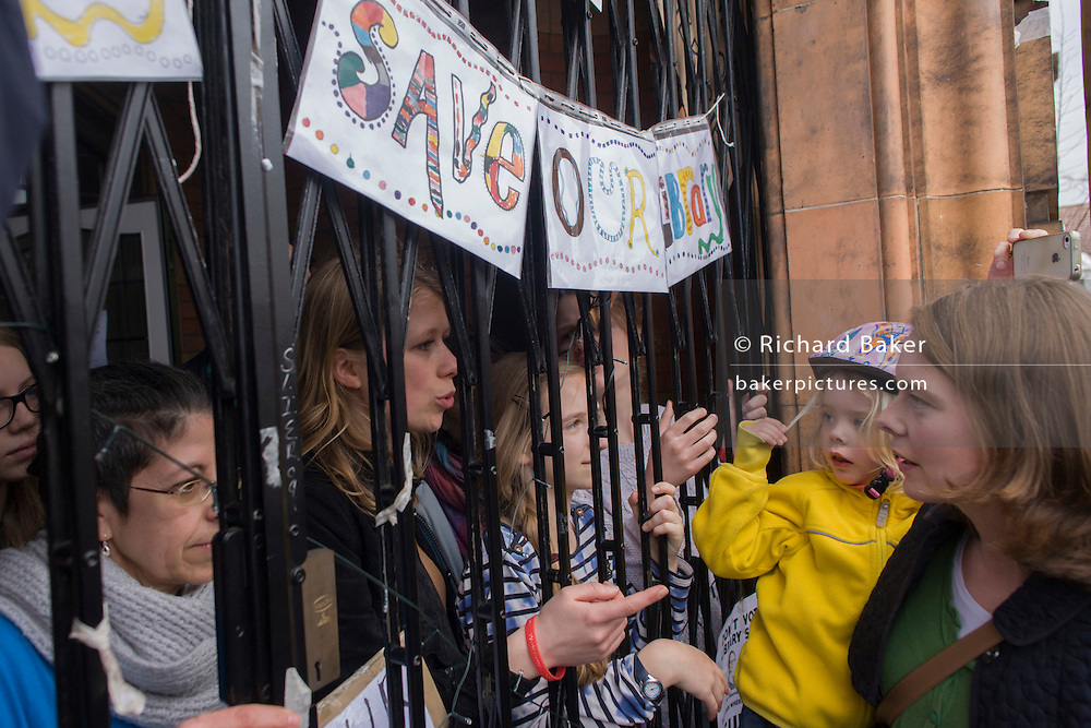 Behind locked gates and receiving thanks from local campaigners, young campaigners protesting the closure by Lambeth council of Carnegie Library in Herne Hill, south London remain inside the premises on day 3 of its occupation, 3rd April 2016. The angry local community in the south London borough have occupied their important resource for learning and social hub for the weekend. After a long campaign by locals, Lambeth have gone ahead and closed the library's doors for the last time because they say, cuts to their budget mean millions must be saved. A gym will replace the working library and while some of the 20,000 books on shelves will remain, no librarians will be present to administer it.