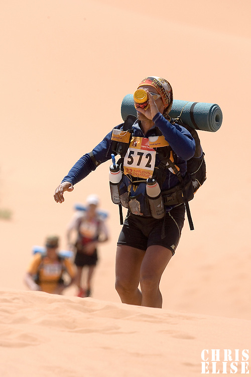 30 March 2007: #572 Juan Antonio Gimenez Munoz of Spain climbs a dune as he drinks water in erg Znaigui en route to check point 3 during fifth stage of the 22nd Marathon des Sables between west of Kfiroun and erg Chebbi (26.22 miles). The Marathon des Sables is a 6 days and 151 miles endurance race with food self sufficiency across the Sahara Desert in Morocco. Each participant must carry his, or her, own backpack containing food, sleeping gear and other material.