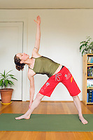 A late 20's woman doing a yoga pose in her apartment...Model Release: 20070608_MR_A