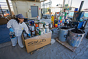 An Hispanic women sorts oil based and latex paint cans at S.A.F.E  Collection Center, Sun Valley, Bureau of Sanitation for the City of Los Angeles, California, USA