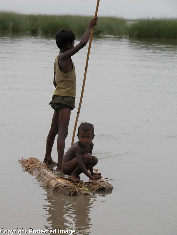 THIS UNIDENTIFIED CHILDREN ARE GOING TO A SAFER PLACE AFTER THEIR HOUSE IS GONE UNDER FLOOD WATER, BIRSHING VILLAGE SOME 345 KILOMETERS OF  GUWAHATI, THE CAPITAL OF NORTHEASTERN INDIAN STATE OF ASSAM, 4TH JULY, 2003. RIVERS SWOLLEN BY INCESSANT   MONSOON RAINS OVERFLOWING WATERS BREAK THE DAMS, DYKES AND BANKS, POURING WATER INTO THE HOMES OF ABOUT 800,000 PEOPLE AND SEVERING TRANSPORTATION LINKS IN NORTHEASTERN INDIA, WHILE MORE THAN THOUSANDS VILLAGES SPREAD OVER 10 DISTRICTS IN THE STATE HAVE BEEN WORSTLY AFFECTED BY THE FLOODS AND THE WATER-BORNE DISEASES LIKE GASTROENTERITIS, DYSENTERY, JAUNDICE AND TYPHOID HIT THE FLOOD-AFFECTED AREAS, WHICH TOOK THE SEVERAL LIVES, OFFICIALS OF  THE FLOOD CONTROL, GOVERNMENT OF ASSAM (INDIA) DEPARTMENT DISCLOSED. (PIC - SHIB SHANKAR CHATTERJEE/AP)