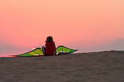 Young boy taking a break from flying kites to watch the sunset over Jockey's Ridge State Park.