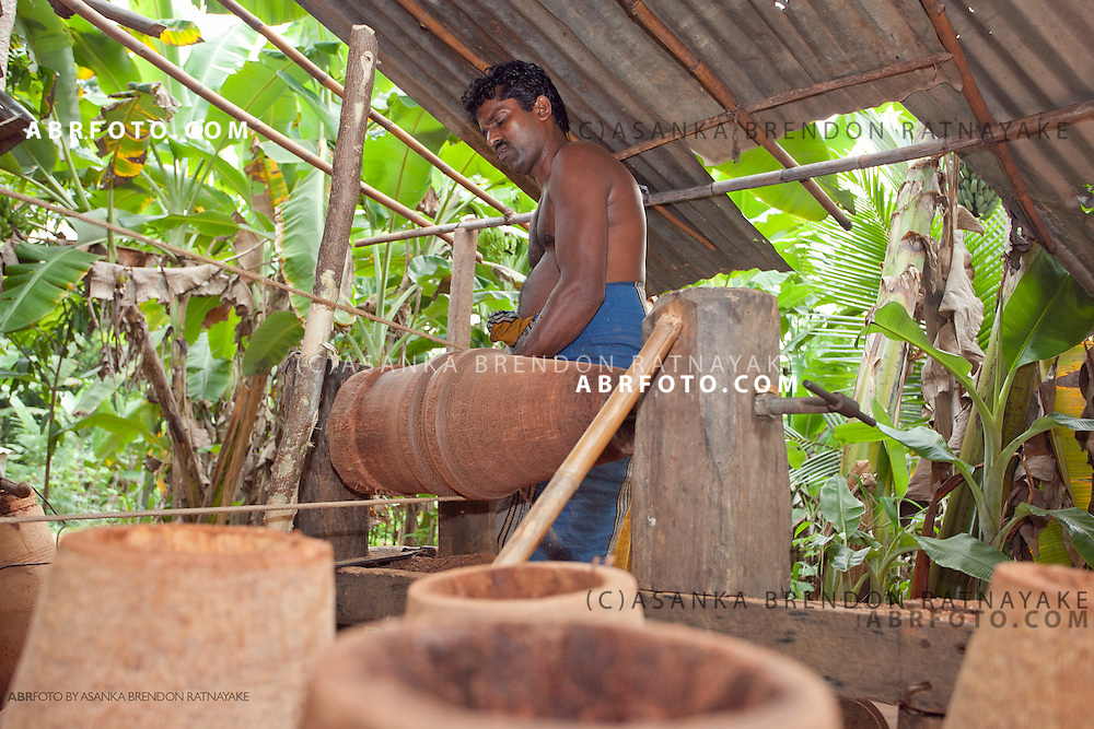 Craftsmen shapes the barrel of the drum using a manually man powered wooden lathe.