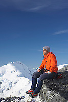 Mountain climber sitting on edge of mountain peak