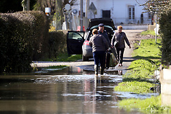 12 March 2020. Beaumerie St Martin, Pas de Calais, France.<br /> Mme Haegeman wades through floods with bags of clothes she is removing from her house as the floodwaters continue to rise inside her flooded home. Following months of record rainfalls, the Canche River near Montreuil Sur Mer burst its banks flooding local homes. The river last flooded in 2013, however residents claim they have never seen it as bad as this.<br /> Photo©; Charlie Varley/varleypix.com