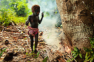 Young Ni Vanuatu boy drying his paint for the snake dance by the fire. Rah Lava Island, Torba Province, Vanuatu
