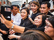 11 NOVEMBER 2016 - BANGKOK, THAILAND: YINGLUCK SHINAWATRA (center left) poses for a selfie with a supporter at a rice distribution sale in the Bangkok suburbs. Yingluck Shinawatra, the former Thai Prime Minister deposed in a coup in 2014, has started selling rice directly to Thai consumers. She buys the rice from farmers at market prices and then sells it to urban consumers at the price she paid. She said she's doing it to help out farmers, who are trying to deal with depressed prices. Yingluck is facing prosecution on corruption related charges going back to a rice price support scheme her government used to try to help farmers in 2011 and 2012. Even after the coup, she is still personally popular and hundreds of people showed up to see her at the rice distribution point at a mall in Samut Prakan province, in suburban Bangkok.   PHOTO BY JACK KURTZ