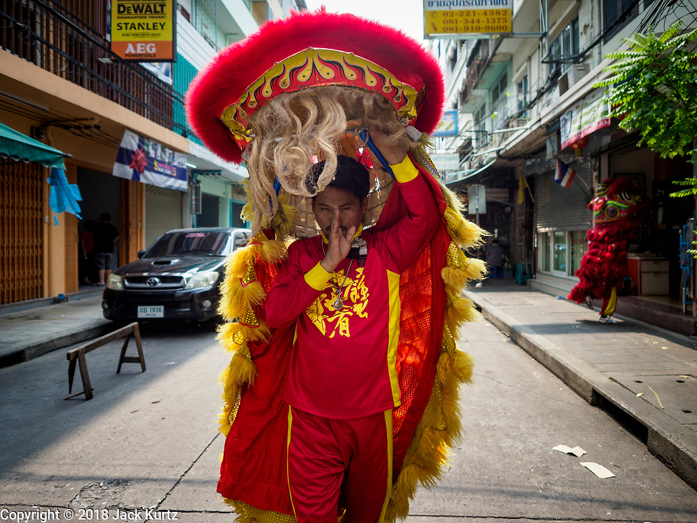 "15 FEBRUARY 2018 - BANGKOK, THAILAND: Chinese ""lion dancers"" walk through Bangkok's Chinatown neighborhood looking soliciting customers. The dancers go door to door looking for people who pay them as a form of merit making. Lunar New Year, also called Tet or Chinese New Year, is 16 February this year. The coming year will be the Year of the Dog. Thailand has a large Chinese community and Lunar New Year is widely celebrated in Thailand, especially in Bangkok and large cities with significant Chinese communities.     PHOTO BY JACK KURTZ"