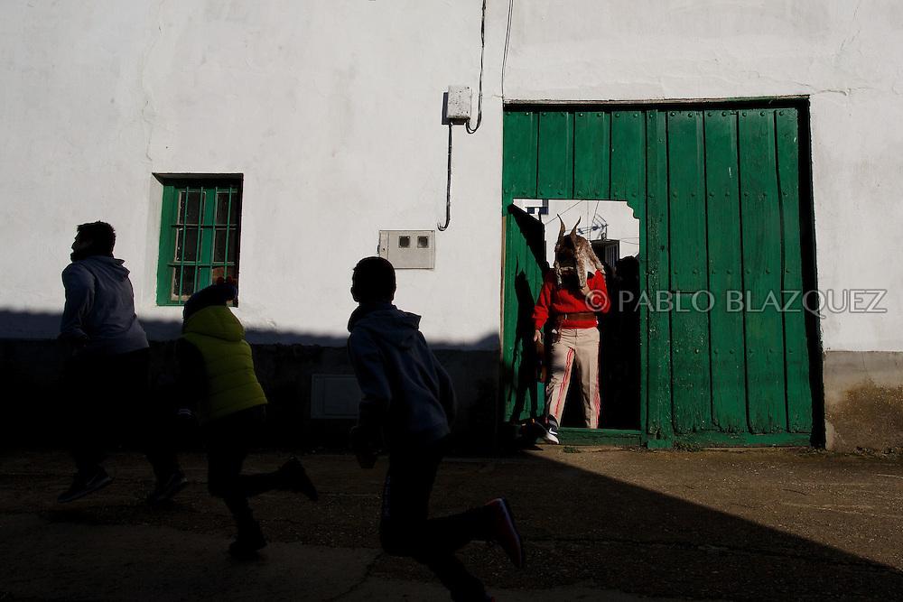 A man dressed as El Diablo leaves a house as children run away during La Filandorra festival on December 26, 2016 in the small village Ferreras de Arriba, Zamora province, Spain.  La Filandorra festival is a pagan winter masquerade that takes place during Saint Esteban festivities. The parade is represented by four characters, La Filandorra, El Diablo (Devil), La Madama (madame) y El Galán (Gallant). (© Pablo Blazquez)