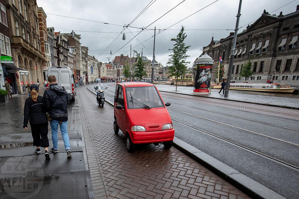 Op het Rokin in Amsterdam rijdt een brommobiel op het fietspad.<br /> <br /> A microcar rides on the bicycle lane at the Rokin in Amsterdam.