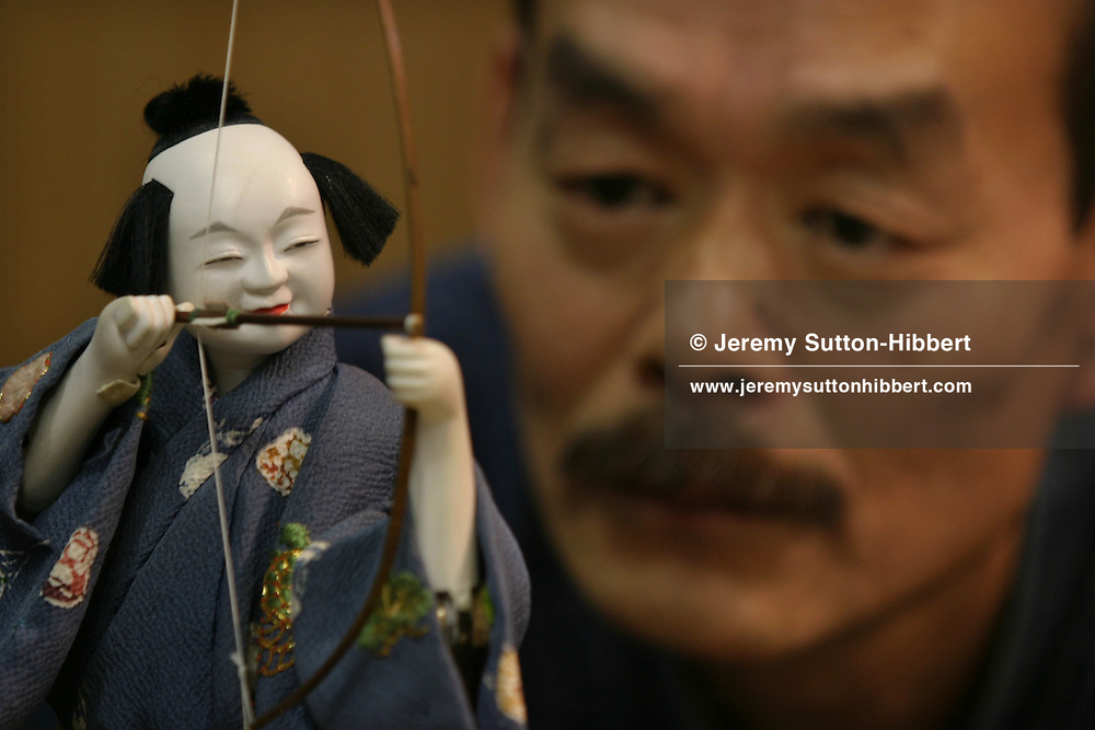 Shobe Tamaya, 9th generation Karakuri-ningyo master, builder of wooden mechanical dolls in the ancient Karakuri tradition. Pictured, in his workshop, with his modern replica wooden doll which fires a bow and arrow, valued at 10 million Yen. Nagoya, Japan.