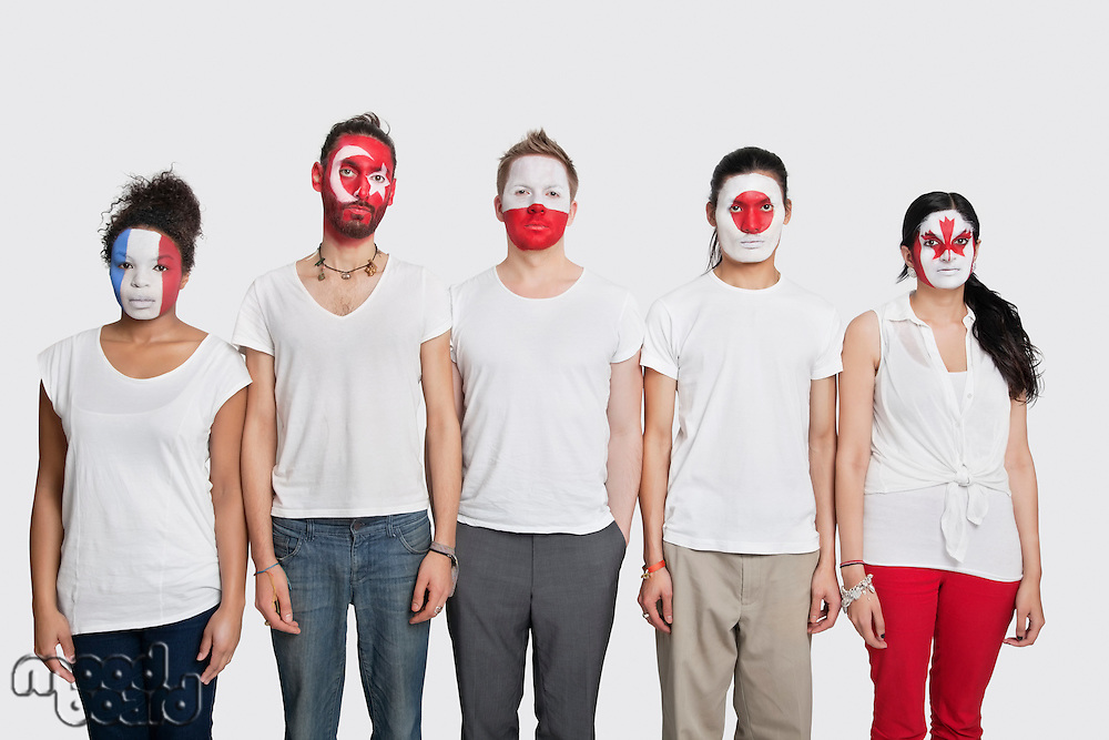Portrait of Multi-ethnic group of friends with various national flags painted on their faces standing at attention against white background