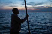 As the sun sets Luke checks fishing weather conditions. Luke, a Folkestone based fisherman out trawling for a 12 hour night solo shift on a fishing trip in his boat Valentine (FE20), Hythe Bay, the English Channel, United Kingdom. (photo by Andrew Aitchison / In pictures via Getty Images)