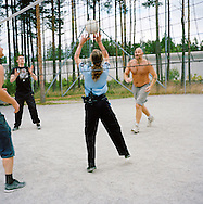 Halden Prison, Norway, June 2014:<br /> Female prison guard playing volleyball with prisoners in the afternoon. <br /> -- No commercial use --<br /> Photo: Knut Egil Wang/Moment/INSTITUTE