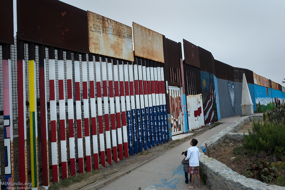 A boy looks at graffiti on an upside down US flag with crosses instead of stars painted along the Mexico-US border. Tijuana, Baja California, Mexico. May 30, 2015.