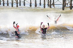 © Licensed to London News Pictures. 07/01/2018. Brighton, UK. Members of the public brave the waves and cold water of the Brighton sea to take part in their daily Exercise. Photo credit: Hugo Michiels/LNP