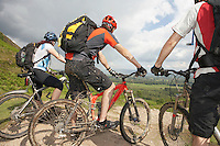 Three cyclists on track in countryside
