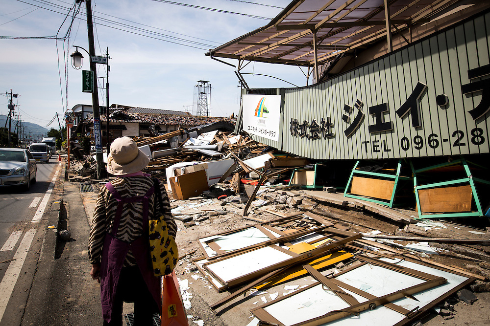 KUMAMOTO, JAPAN - APRIL 20 : A woman is seen through the wreckage of houses on April 20, 2016 in Mashiki town, Kumamoto, Japan. At least 41 people were killed and over 180,000 people were evacuated in the series of earthquakes hitting southwestern Japan since 14 April 2016.<br /> Photo: Richard Atrero de Guzman