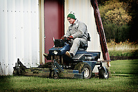 A farmer mows the lawn near his machine shed, Birch Hills, SK.