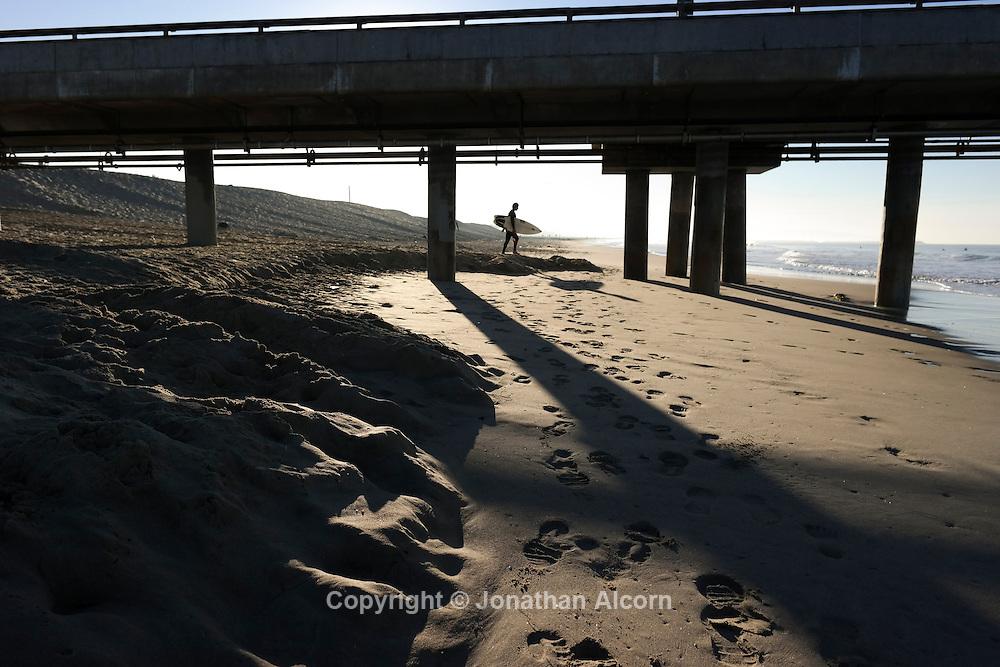 A surfer under the Venice Pier on December 14, 2013.  NX 300 17mm lens ©Jonathan Alcorn