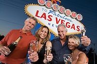 Two women and two men posing in front of Welcome to Las Vegas sign, group portrait.