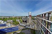 Nederland, Nijmegen: 1-5-2018 Uitzicht op het centum van Nijmegen richting Betuwe . Linksonder het politiebureau, ertegenover het voormalige belstingkantoor, belastinggebouw, waar een tijdelijk azc en studentenhuisvesting in zit, de stevenskerk, rivier de waal en de nevengeul, spiegelwaal zijn te zien . FOTO: FLIP FRANSSEN
