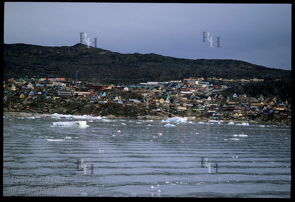 Colorful village homes line rocky shore overlooking small icebergs and calm August seas of Disko Bay; Ilulissat, Greenland