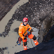 "Rope access technician Haukur Grönli working on the removal of safety nets, in the canyon ""Hafrahvammagljúfur"", at Kárahnjúkar dam area, Iceland. Safety nets were put up to prevent rockfall onto workers, working on the lower dam."