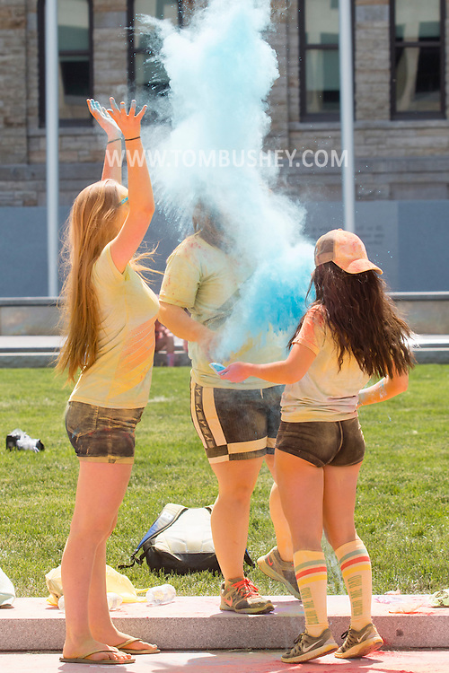 Scranton, Pa. - Colorful powder fills the air as three girls toss color packets on the stage after the Color Me Rad 5K color run on May 24, 2015.
