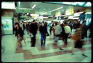 Rush of commuters blurs past blue-jean clad young woman as she walks through Tokyo Station. Japan