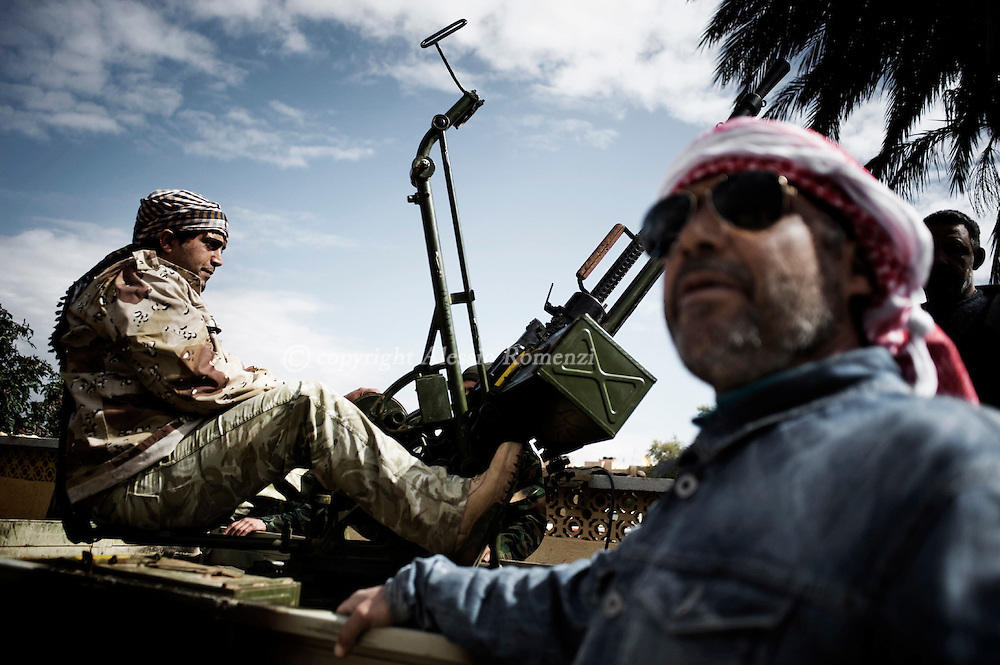 Libya, Benghazi. A defected army commando sitting on an anti-aircraft  gun next an anti-Kadahfi supporter on February 26, 2011. ALESSIO ROMENZI