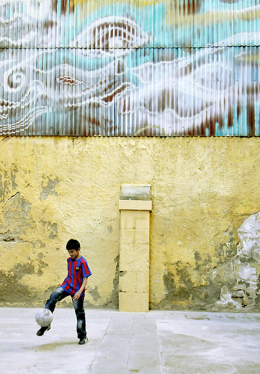 A boy wearing an FC  Barcelona soccer shirt juggles a soccer ball in a colorful alley in the El Borne section of Barcelona.