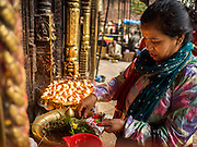 01 AUGUST 2015 - KATHMANDU, NEPAL:  People light butter lamps and pray at Seto Machindranath Temple, a Hindu temple near Durbar Square in Kathmandu, Nepal.  The temple was undamaged in the Nepal Earthquake, although neighboring homes and the wall around the temple were destroyed.    PHOTO BY JACK KURTZ